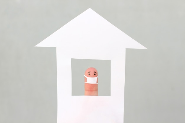 집에서 얼굴 마스크를 쓴 외로운 남자의 손가락 예술.