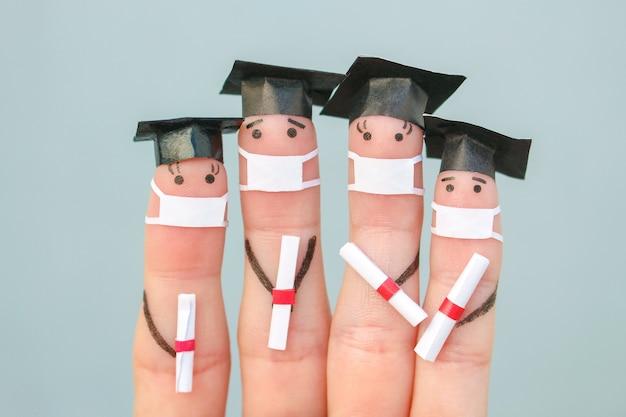 Covid-2019からの医療マスクの学生の指の芸術。卒業後に卒業証書を保持している卒業生。