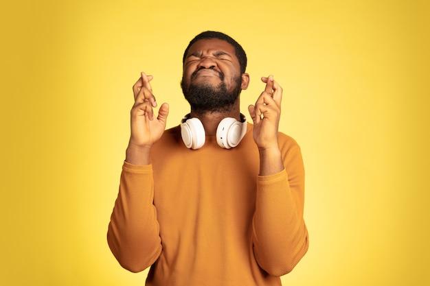 손가락이 교차했습니다. 행운을 빕니다. 노란색, 표정에 젊은 아프리카계 미국인 남자의 초상화. 헤드폰, copyspace와 아름 다운 남성 모델입니다. 인간의 감정, 판매, 광고의 개념입니다.