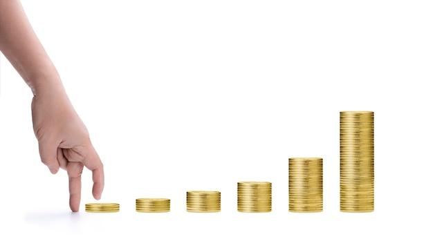 指は、テキストスペースのある白い背景の利益のグラフチャートのように、金貨のスタックを手で踏み出します。ビジネスファイナンスの成長コンセプトのアイデア。将来の生活コンセプトへの投資を開始します。