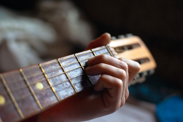 Fingers hold the chord fretboard acoustic guitar.