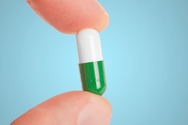 Пальцы держат таблетки капсулы, изолированные на белом фоне