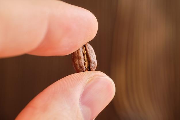 Пальцы держат жареного кофе на деревянных, размытый фон.