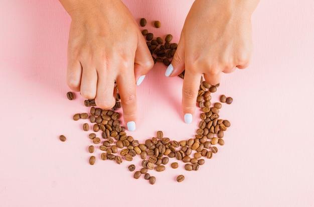 Пальцы, делающие сердечный разрыв из кофейных зерен