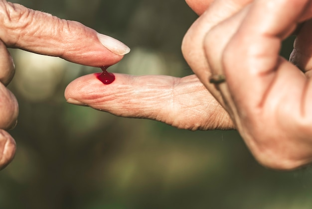 Fingers of man and older woman with blood