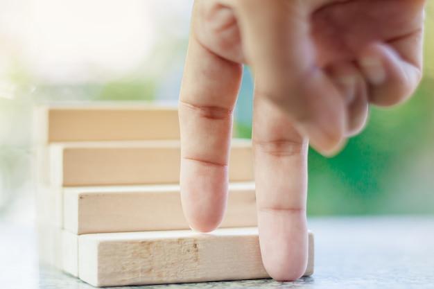 指がぼんやりとした自然の緑色の背景に対して木製の玩具の階段を上げていく