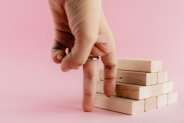 Fingers moving step up the wooden toy staircase