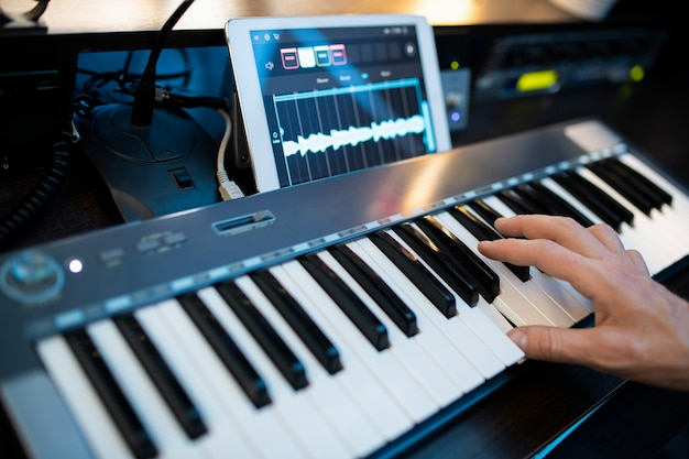 Пальцы молодого современного пианиста нажимают клавиши фортепианной клавиатуры во время записи музыки на рабочем месте в студии