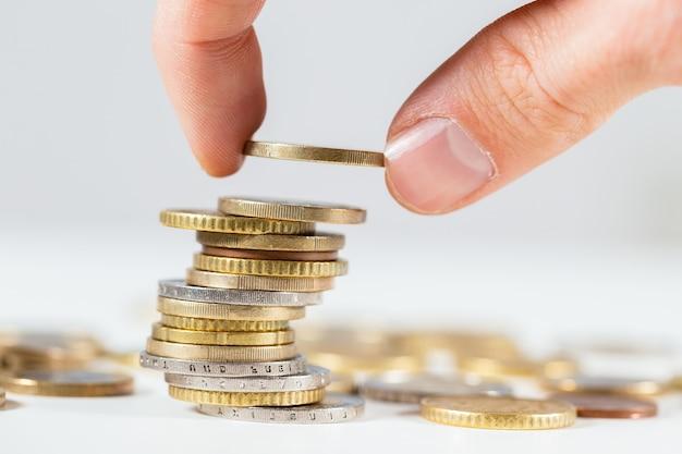 クローズアップからコインの山に1ユーロを置く指