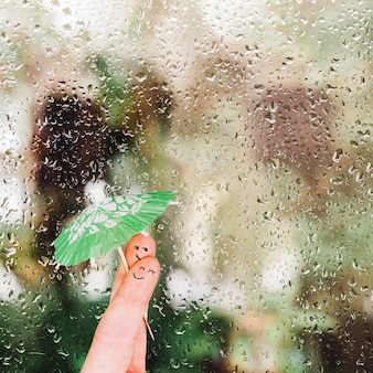 Fingers with umbrella near glass with raindrops