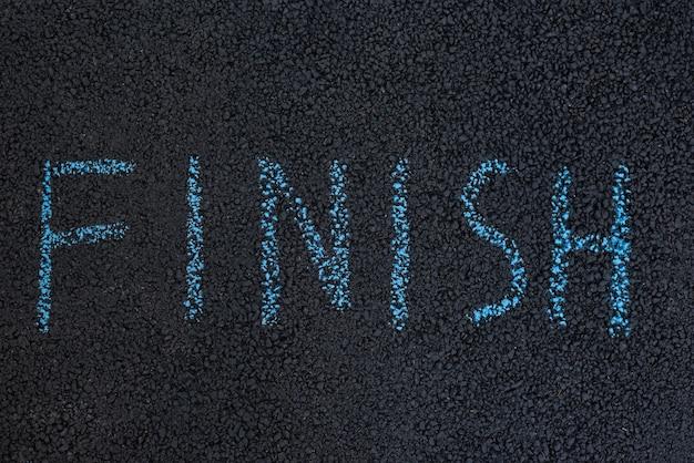 Текст finish под ногами. черный асфальт с надписью мелом. концепция конца