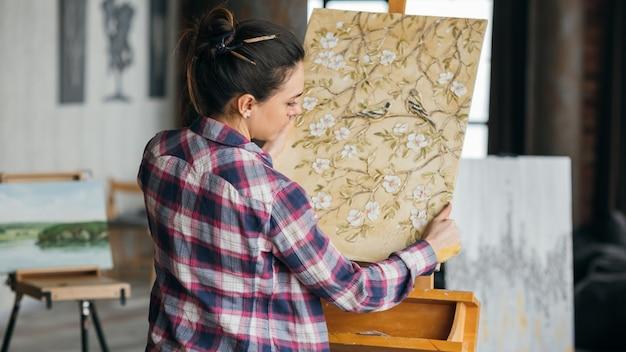 完成したアートワーク。花と鳥の帆布。アートスタジオのワークスペース。絵画を見ている女性アーティスト