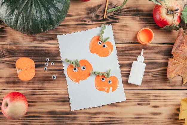 Finished halloween card made with pumpkin apple prints lies next to glue and paint on wooden surface, top view