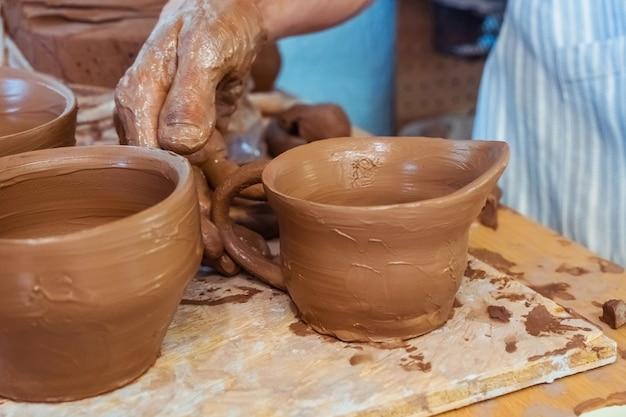 완성 된 생 점토 컵은 테이블에서 건조됩니다. 점토에서 완성 된 주전자까지의 도자기