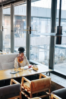 Завершающий проект. занятый, умный молодой фрилансер заканчивает свой проект сидя в ресторане