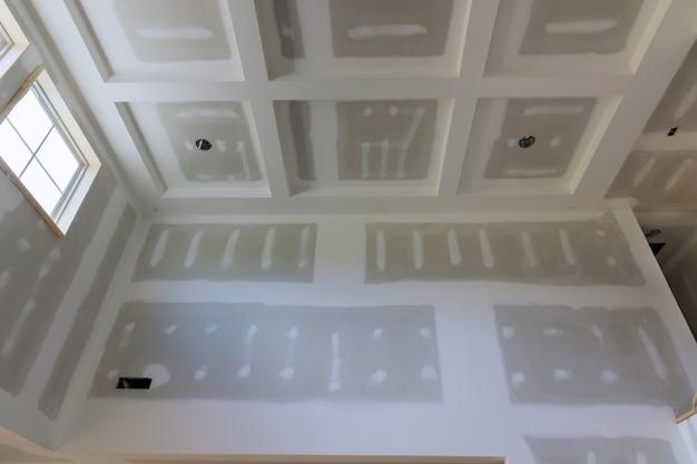 천장과 벽에 집이 있는 주걱으로 건식 벽체에 퍼티 마무리