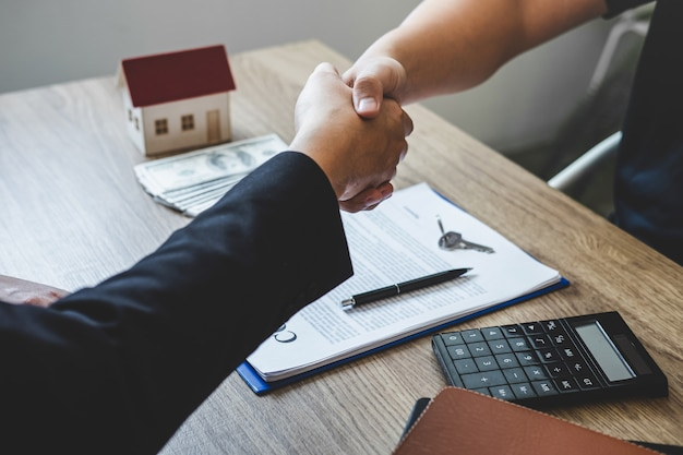 Finishing to successful deal of real estate, broker and client shaking hands after signing contract approved application form, concerning mortgage loan offer for and house insurance