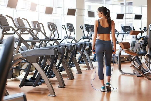 ジムに立っているスポーツウェアの短くてスリムな若い女性の仕上げトレーニング背面図