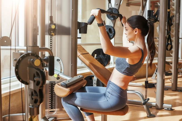Finishing workout back view of short and slim young woman in sportswear standing at gym