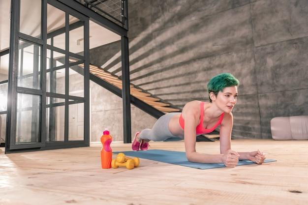 운동 끝내기. 널빤지로 운동을 마치면서 진정으로 만족하고 활력을 느끼는 슬림 여성