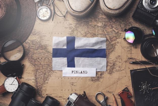 古いビンテージ地図上の旅行者のアクセサリーの間フィンランドフラグ。オーバーヘッドショット