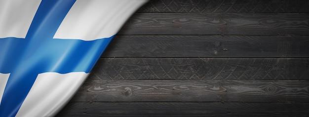 黒い木の壁にフィンランドの旗。水平方向のパノラマバナー。