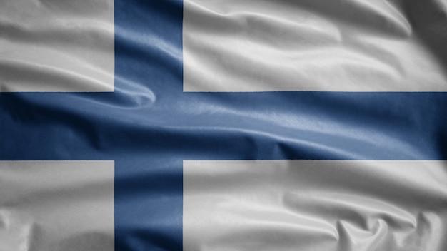 風に手を振るフィンランドの旗。フィンランドのバナーを吹く、柔らかく滑らかなシルクのクローズアップ。