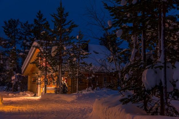 핀란드 라플란드. 밤 겨울 숲에서 코 티 지입니다. 많은 눈