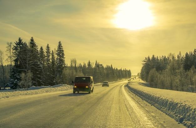 핀란드 라플란드. 겨울 숲 도로와 태양. 자동차와 버스