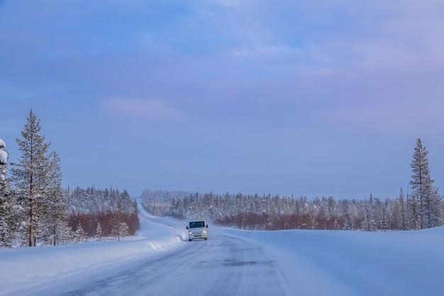 핀란드 라플란드. 석양 겨울 숲 도로입니다. 외로운 버스