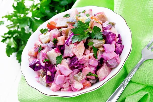 청어, 비트 뿌리, 감자, 절인 또는 절인 오이, 당근, 양파, 계란을 곁들인 핀란드 로솔리 샐러드, 흰색 나무 판자 배경에 있는 그릇에 마요네즈를 곁들인
