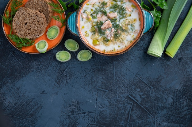 Финский суп из лосося с луком-пореем и сливками. вид сверху на темный стол.