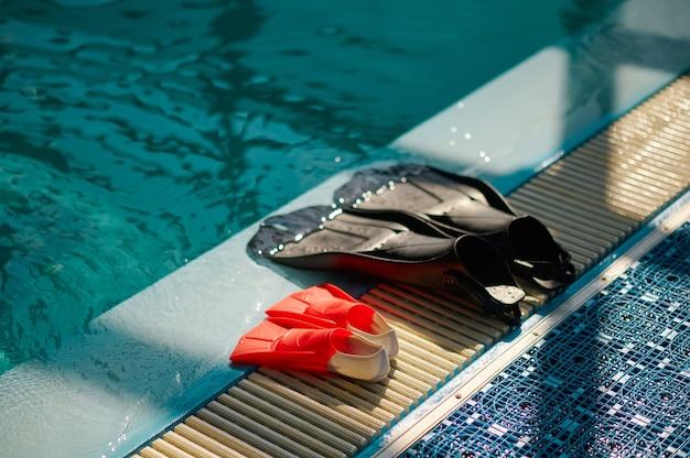 Ласты у бассейна, акваланг, снаряжение для дайвинга, никто. обучение людей плаванию под водой, интерьер крытого бассейна на заднем плане, ласты для дайверов