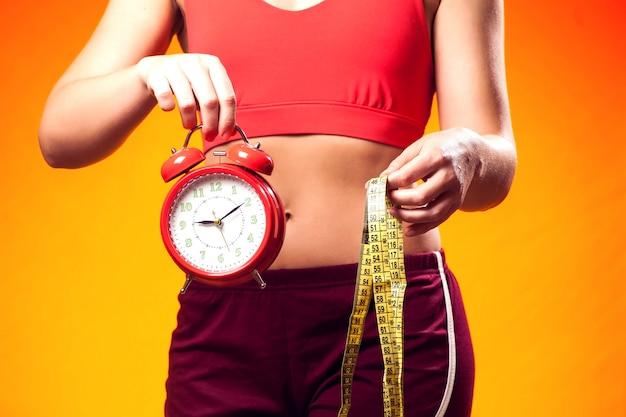 目覚まし時計とメーターを保持しているスポーツウェアの女性。 fintess時間とダイエットのコンセプト