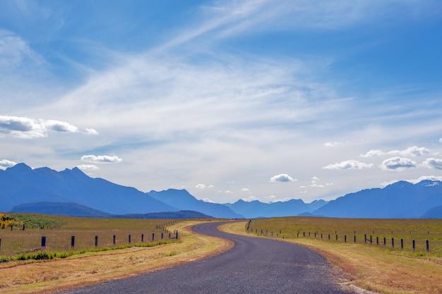 Пасторальная извилистая проселочная дорога и горы в fiordland, новая зеландия