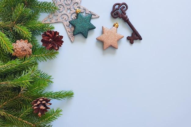青いテーブルの上のモミの境界線、星、鉄の鍵、松ぼっくり。クリスマスフレームの上面図