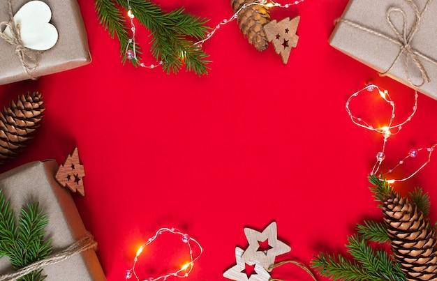 Еловая ветка, подарочная коробка, гирлянда и елочные игрушки на красном фоне. экологичные материалы.