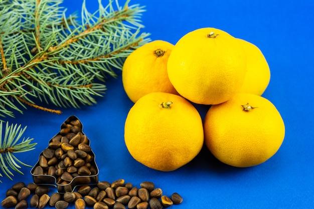 Еловая ветка, орехи в виде елки и мандарины на синем фоне.