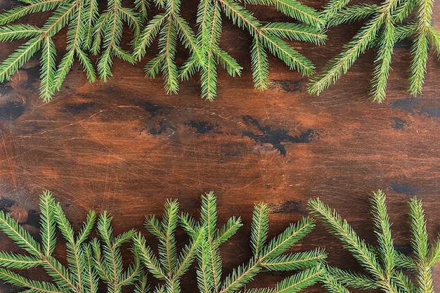 나무 빈티지 크리스마스 배경에 전나무 지점입니다. 나무 테이블에 있는 크리스마스 전나무와 가문비나무 가지의 겨울 갈색 배경, 평평한 평지, 꼭대기 전망. 크리스마스와 새해 테두리