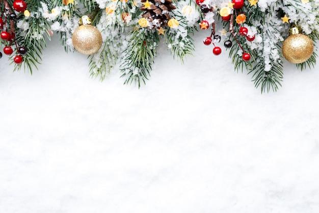 Еловая ветка с елочными украшениями на фоне натурального снега