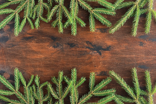 Fir branch on wooden vintage christmas background. winter brown background of christmas fir and spruce branches on wooden table, flat lay and top view. xmas and new year border