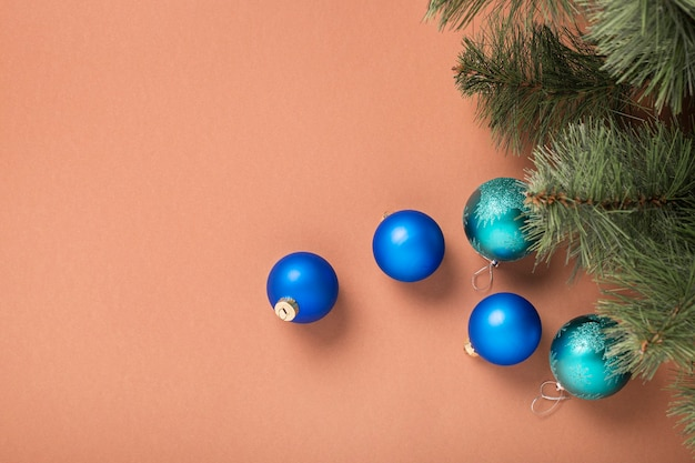 Еловые ветки и елочные украшения на коричневом фоне. концепция на новый год и сочельник. баннер.