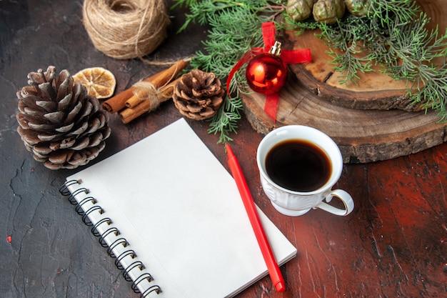 モミの枝とペンシナモンライム針葉樹の円錐形と暗い背景に紅茶のカップと閉じたスパイラルノート