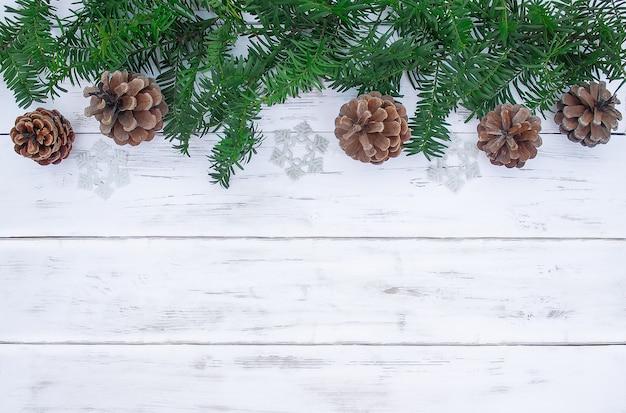 白い木の板にモミの枝と松ぼっくり