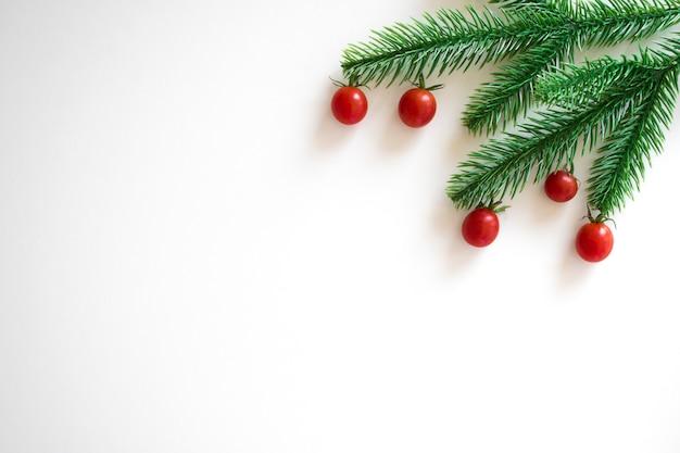 モミの枝と白地に小さな赤いチェリートマト。コピースペースとクリスマスの背景。