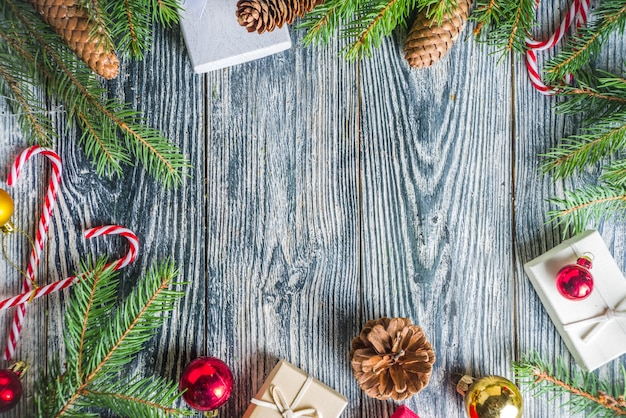 Fir branches and christmas ornaments on wooden background
