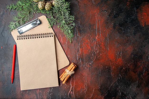 Еловые ветки корицы, лаймы, хвойные шишки, подарок и блокнот на темном фоне