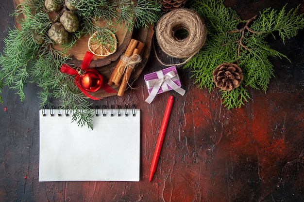 Fir branches and closed spiral notebook with pen cinnamon limes ball of rope on dark background