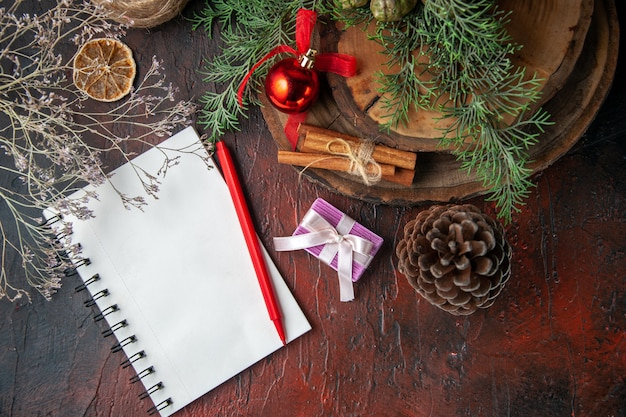 Fir branches and closed spiral notebook with pen cinnamon limes conifer cone and ball of rope on dark background above view