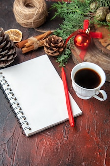 Fir branches and closed spiral notebook with pen cinnamon limes conifer cone and a cup of black tea on dark background